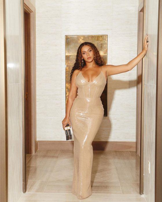 Beyoncé recargada en el marco de una puerta usando un vestido de color dorado con el cabello rizado