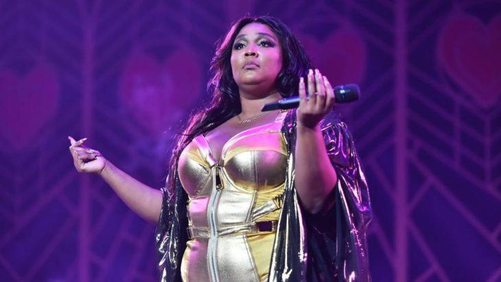 Cantante Lizzo en uno de sus conciertos usando un vestido de color dorado