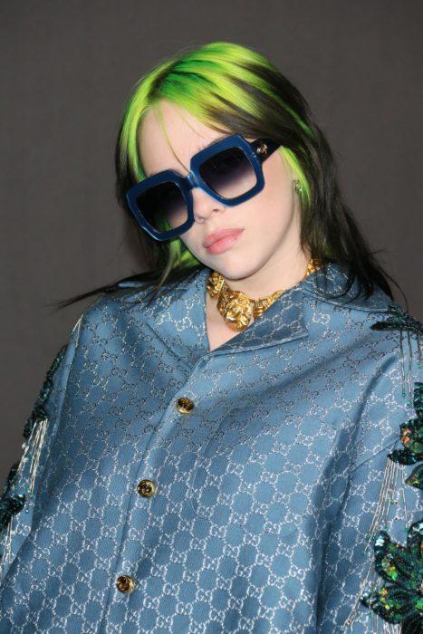 Cantante Billie Eilish usando un saco azul, lentes de sol azul y el cabello teñido de color verde