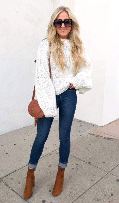 Chica usando unos jeans de color azul, suéter de color blanco y botines color camel