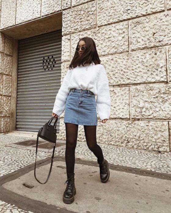 Chica usando una falda de mezclilla con un suéter grande y abrigador de color blanco
