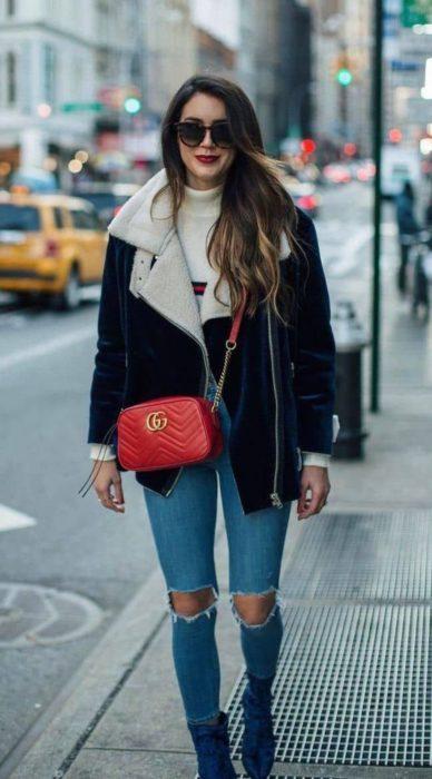Chica caminando por la calle mientras usa un atuendo de chaqueta negra con una chaqueta de color negro, jeans y bolsa cruzada sobre el pecho