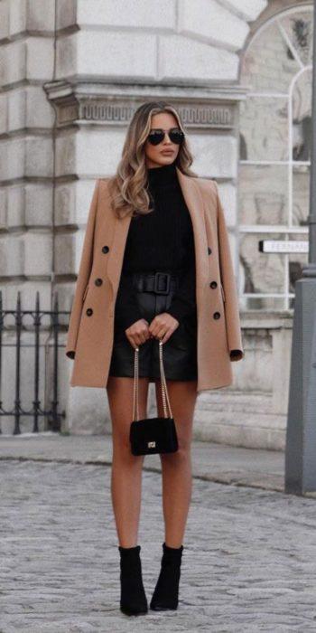 Chica usando un abrigo de color camel con un atuendo de blusa y falda de color negro