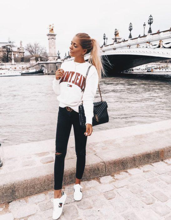 Chica usando una sudadera de color blanco con jeans y tenis del mismo color