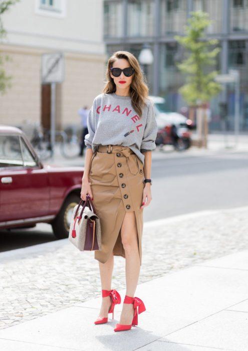 Chica usando una falda de color camel con zapatos rojos y sudadera de color gris