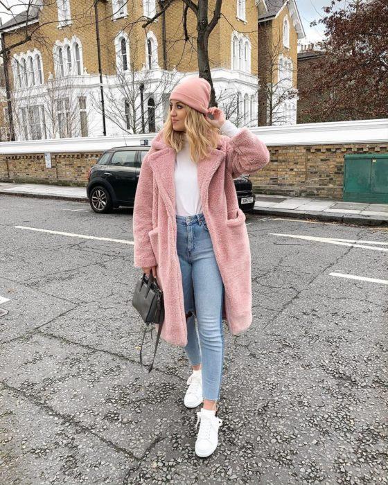 Chica usando un abrigo de color rosa con unos jeans azules y blusa de color blanco como los tenis