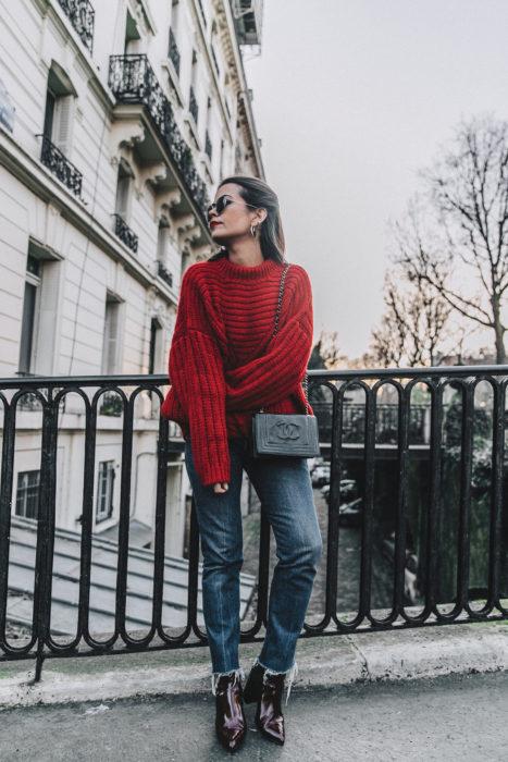 Chica usando un sueter de color rojo con jeans y botines de charol en color vino