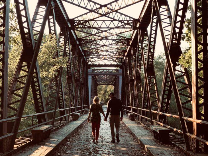 Escena de la película A quiet place 2 pareja caminando por un puente de madera
