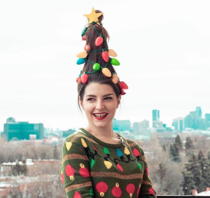 Chica llevando suéter navideño posando para una foto sobre una montaña