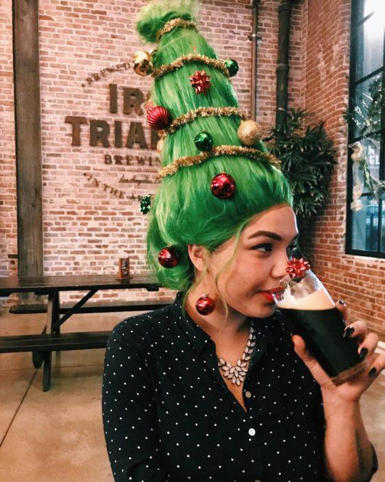 Chica llevando un peinado alto con cabello en verde y esferas en rojo