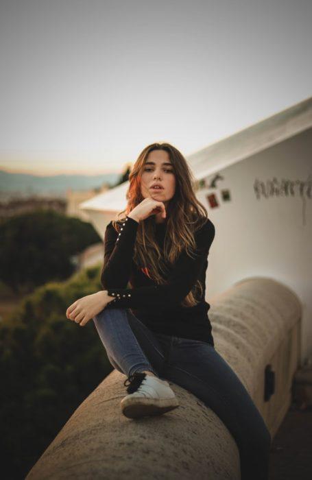 Chica sentada en la orilla de una banqueta