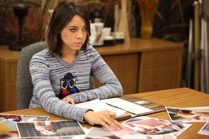 Chica sentada frente a un escritorio, molesta
