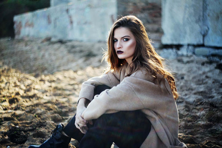Chica ruda sentada sobre hojas secas