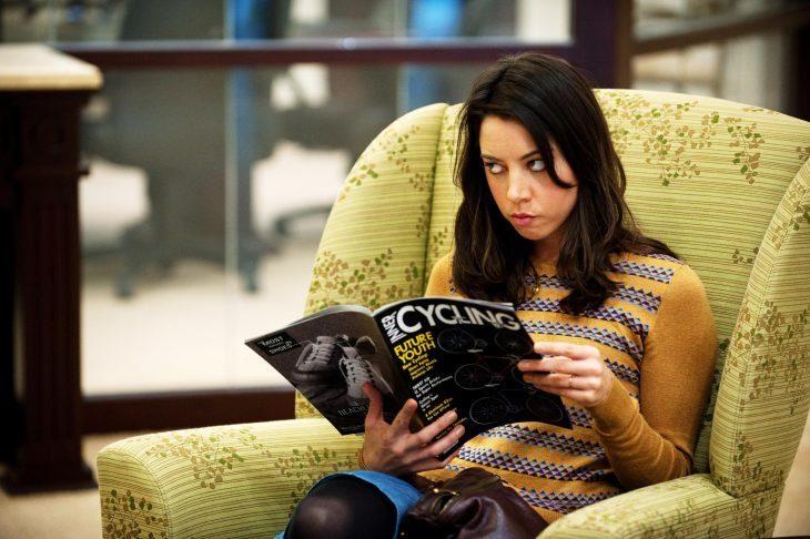 Chica molestando mirando sobre una revista