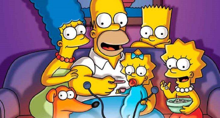 Personajes de la serie Los Simpson viendo la televisión en la sala de su casa