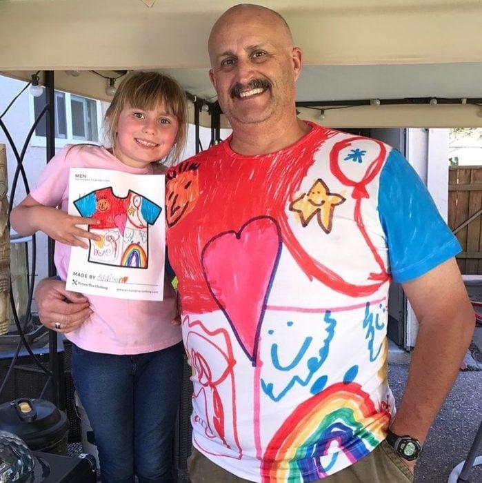 Ppá abrazando a su hija llevando una camisa con los dibujos que ella hizo
