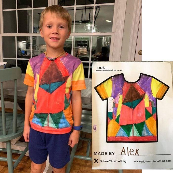 Niño posando una camisa que previamente diseño y coloreo