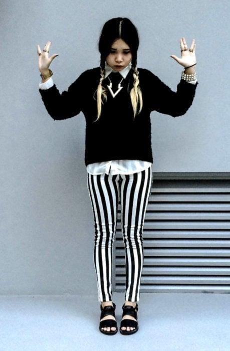 Chica vestida de Merlina Adams; con suéter negro, pantalón de rayas blancas, peinada con trenzas