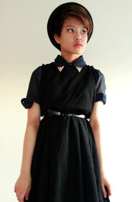 Chica vestida de Merlina Adams; vestido negro con cuello dorado, sombrero y cinto