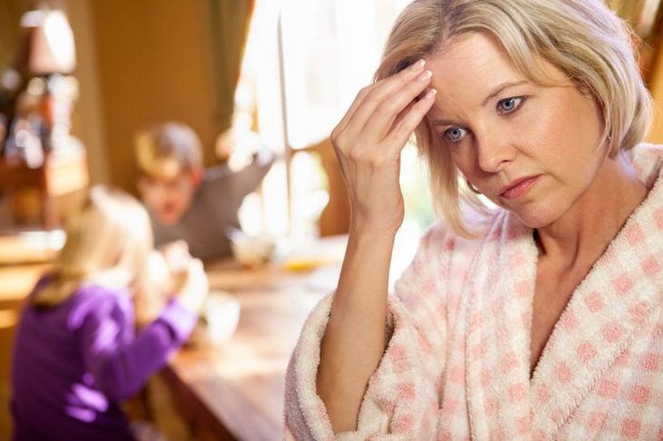 Donna che guarda frustrata mentre i suoi figli combattono