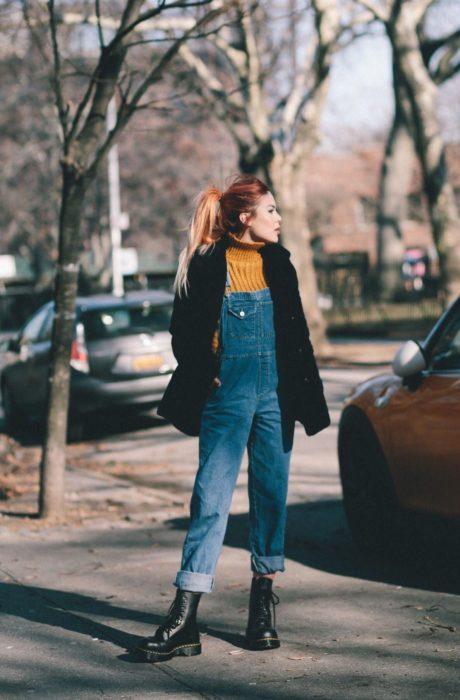 Chica usando un overol con un bluson amarillo y saco de color negro