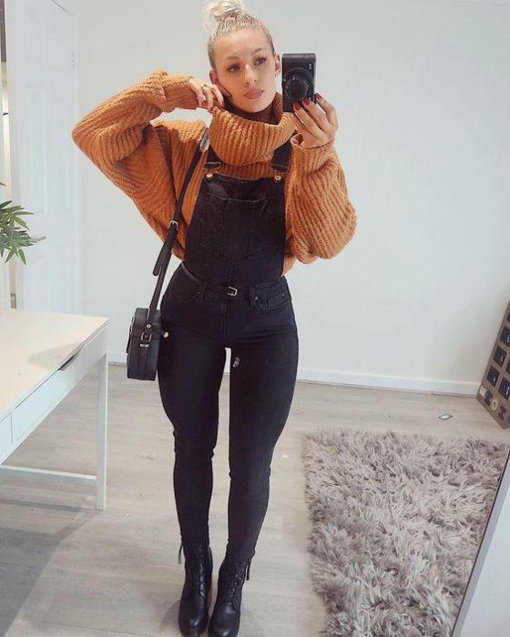 Chica tomándose una selfie mientras usa un overol negro con un suéter de color naranja