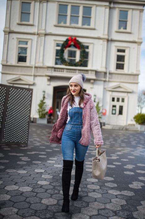 Chica usando un overol con botas altas de color negro, suéter rosa y gorro de lana