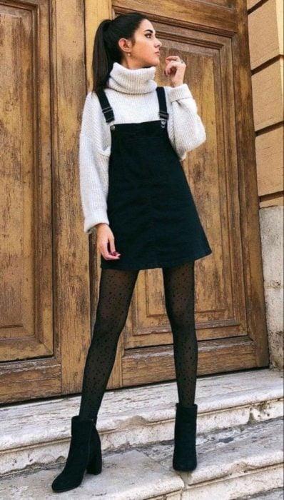 Chica usando un overol de color negro con un suéter de color beige