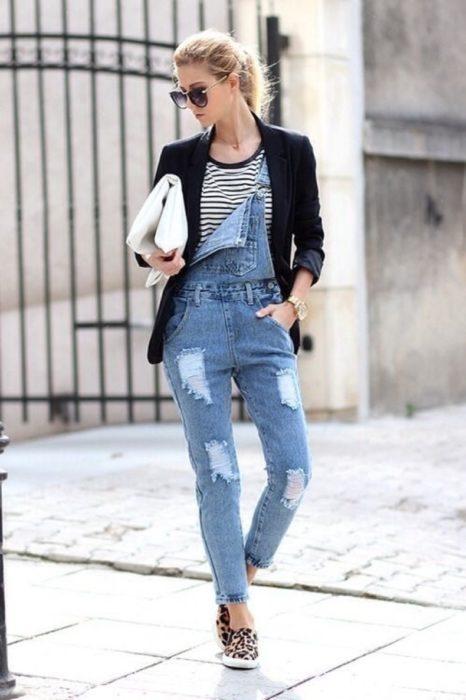 Chica usando un overol con un blazer negro, bolsa de mano y tenis de leopardo
