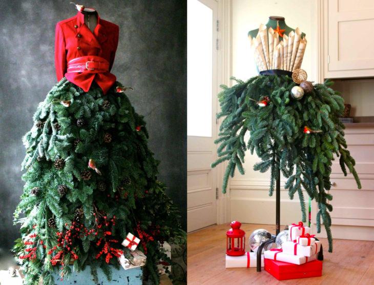 Árbol verde de Navidad como vestido de maniquí, con saco rojo y top formado por partituras de villancicos, con regalos
