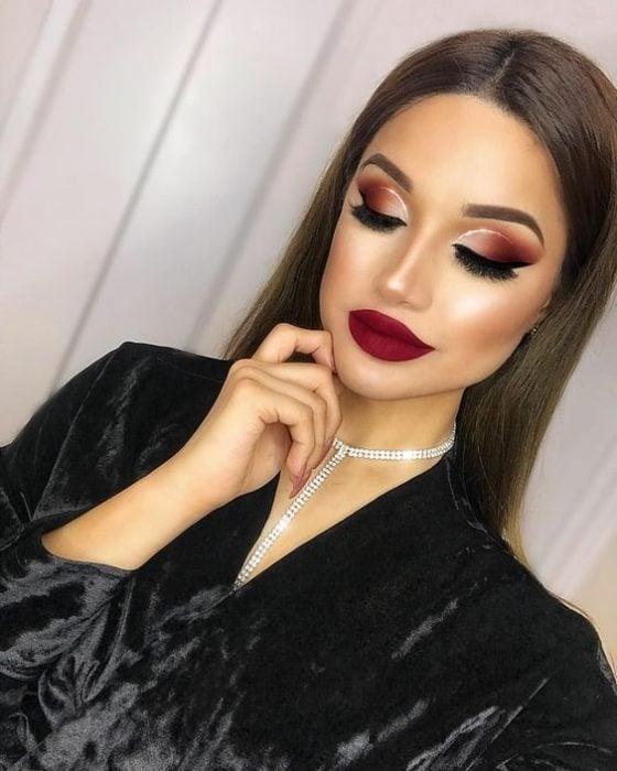 Chica mirando hacia abajo mostrando maquillaje en rojo y dorado