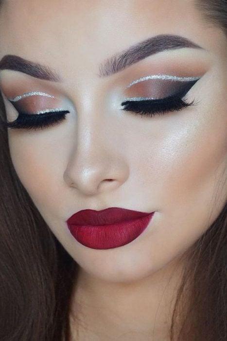 Chica ojos cerrados mostrando maquillaje cono delineado en glitter