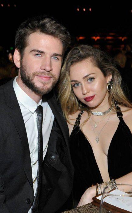 Miley Cyrus y Liam Hemsworth posando para una foto mientras están sentados en una cena