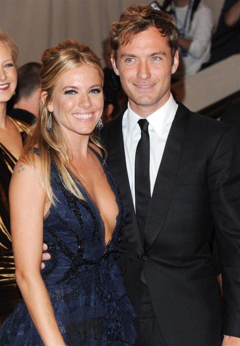 Jude Law y Sienna Miller abrazados mientra están sonriendo para una fotografía