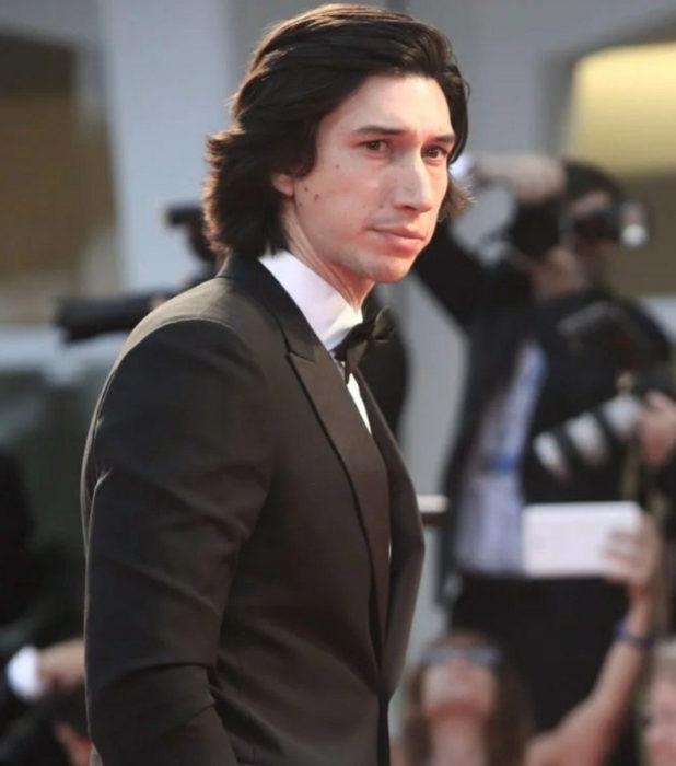 Actor Adam Driver; hombre de traje negro, cabello oscuro y largo