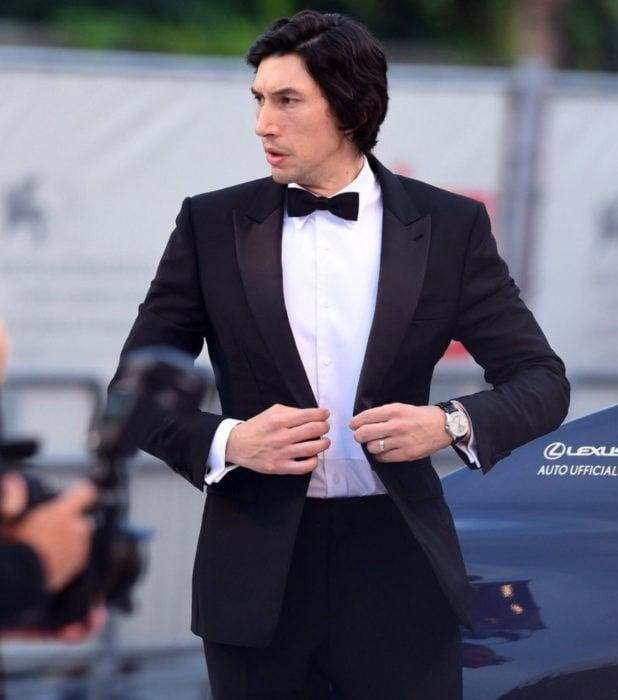 Actor Adam Driver; hombre de cabello oscuro y largo, abrochándose el saco de vestir