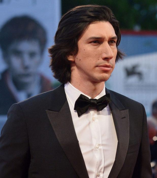 Actor Adam Driver; hombre de cabello negro y largo con traje y moño
