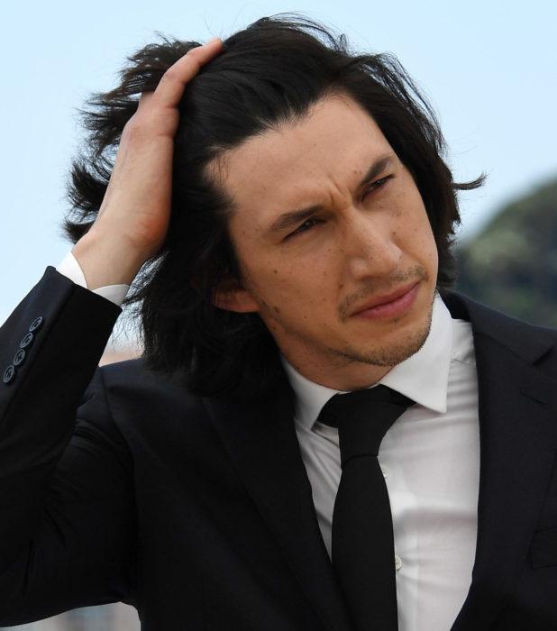 Actor Adam Driver; hombre de traje y corbata, acomodándose el cabello negro y largo