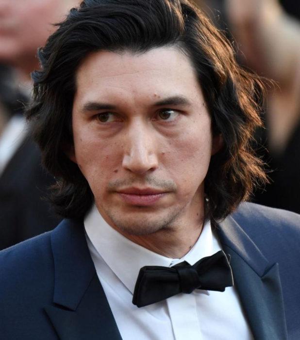 Actor Adam Driver; hombre con traje azul, moño, cabello largo y negro