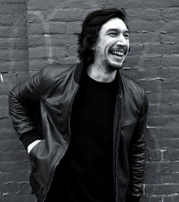Actor Adam Driver; fotografía en blanco y negro de hombre recargado en la pared sonriendo, con chamarra de cuero, cabello largo y oscuro, barba y bigote