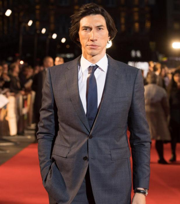 Actor Adam Driver en la alfombra roja; hombre con traje gris, corbata azul, cabello largo
