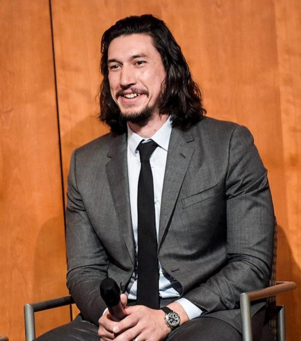 Actor Adam Driver; hombre sentado con micrófono en mano, cabello largo y negro, barba y bigote