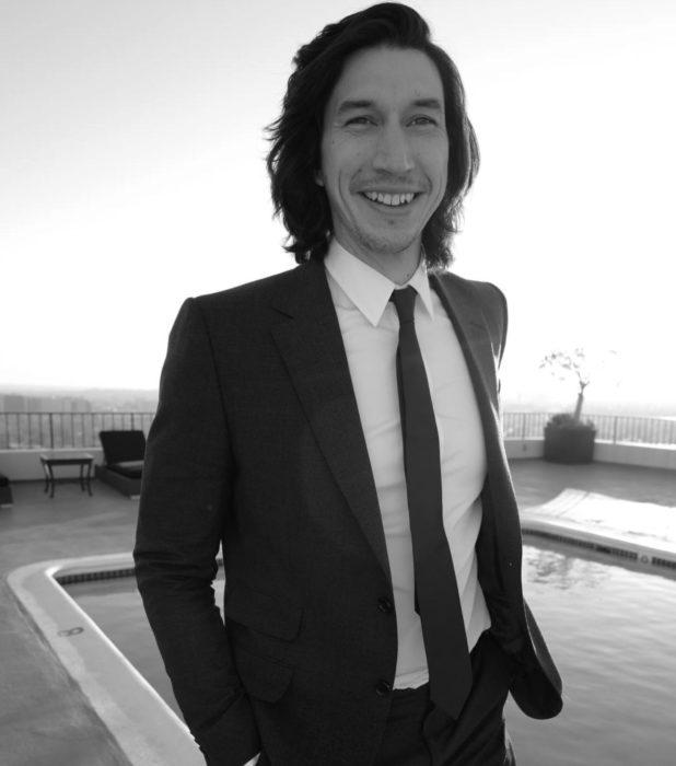 Actor Adam Driver; hombre con traje, saco y corbata, de cabello negro, largo y lacio, sonriendo