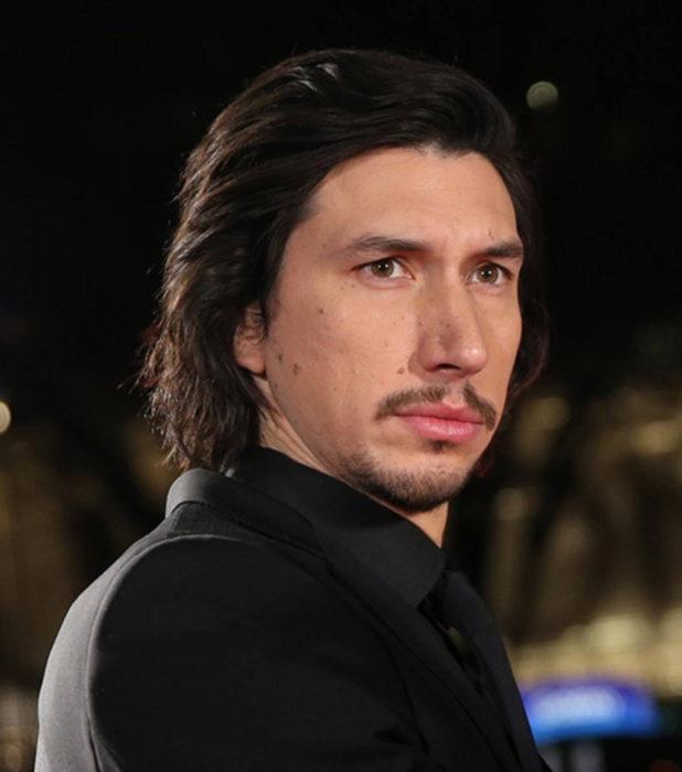 Actor Adam Driver; hombre con traje, cabello oscuro, ojos verdes. barba y bigote