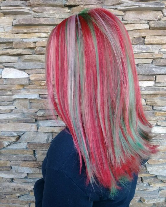 Chica con el cabello teñido de color rojo con azul y luces en tonos platinados