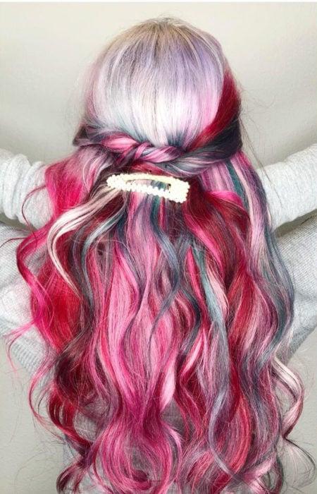 Chica con el cabello rizado y teñido de colores rojo, azul, verde y platinado