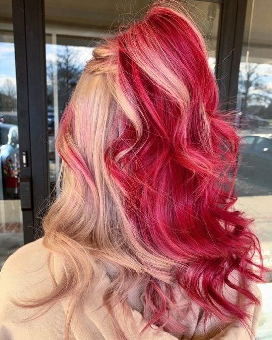 Chica con el cabello teñido de color caramelo con tintes rubios y rojos