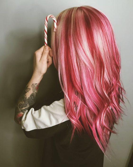 Chica con el cabello de color rojo con rosa para la tendencia candy cane