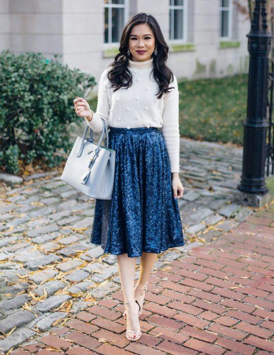 Pantone elije el classic blue como el color del 2020; mujer con falda azul clásico de terciopelo, blusa blanca y bolsa grande de mano