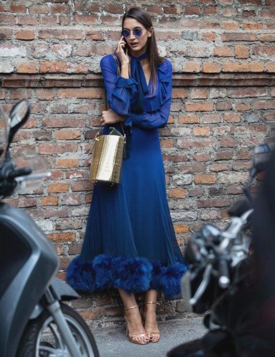 Pantone elije el classic blue como el color del 2020; mujer recargada en la pared, hablando por celular, con vestido azul clásico y bolsa dorada